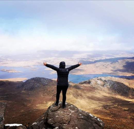 Standing on the ledge of Stac Pollaidh NC500